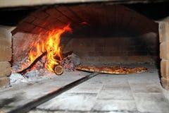 Hornada de la pizza en horno encendido madera Foto de archivo libre de regalías