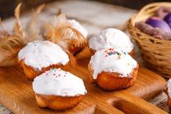 Hornada de Pascua con la formación de hielo del azúcar en un tablero adornado con las plumas y una cesta con los huevos pintados Foto de archivo libre de regalías