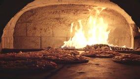 Hornada en el horno de madera, quema de la pizza de las llamas metrajes