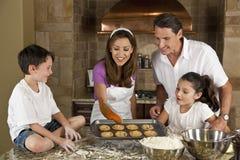 Hornada feliz de la familia y galletas de la consumición en una cocina Fotografía de archivo