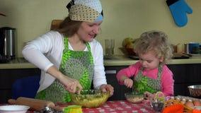 Hornada feliz de la madre con la pequeña hija en delantal muchachas de la familia en cocina metrajes