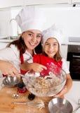 Hornada feliz de la madre con la pequeña hija en harina de mezcla del sombrero del delantal y del cocinero en la cocina fotos de archivo