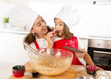 Hornada feliz de la madre con la pequeña hija que come la barra de chocolate usada como ingrediente mientras que enseña al niño foto de archivo libre de regalías