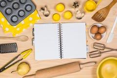Hornada y herramientas de los pasteles con el cuaderno Fotos de archivo libres de regalías