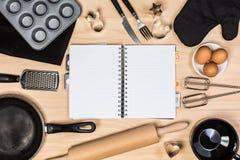 Hornada y herramientas de los pasteles con el cuaderno Imágenes de archivo libres de regalías