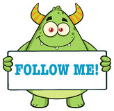Horned Green Monster. Cartoon Character Holding Follow Me Sign Royalty Free Stock Photo