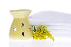 Hornilla de petróleo, flor amarilla y toalla blanca Imagenes de archivo