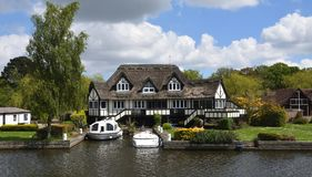Luxury Property on the banks of the river Bure at Horning Norfolk England. HORNING, NORFOLK, ENGLAND - MAY 10, 2018: Luxury Property on the banks of the river royalty free stock photos