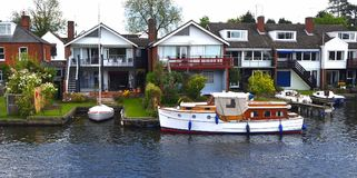 Waterside properties and old fashioned cruiser on the river Bure at Horning. stock photography