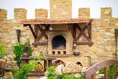 Horno antiguo ahumado del ladrillo al aire libre con la leña, platos Fotografía de archivo libre de regalías