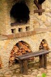 Horno antiguo ahumado del ladrillo al aire libre con leña y un banco Foto de archivo