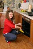 Horno de la cocina de la limpieza de la mujer Imágenes de archivo libres de regalías