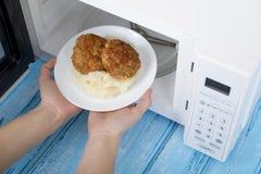 Horno de microondas blanco, en una superficie de madera azul para la comida de calefacción Fotos de archivo