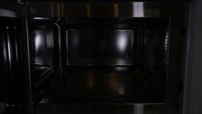 Horno de microondas elegante y nuevo moderno, visión dentro, primer almacen de metraje de vídeo