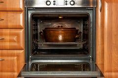 Horno nacional eléctrico y pote de cerámica Platos de la hornada para la carne Preparación de la comida en el horno Fotografía de archivo