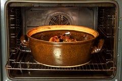 Horno nacional eléctrico y pote de cerámica Platos de la hornada para la carne Preparación de la comida en el horno Fotografía de archivo libre de regalías