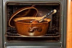 Horno nacional eléctrico y pote de cerámica Platos de la hornada para la carne Preparación de la comida en el horno Foto de archivo libre de regalías