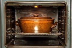 Horno nacional eléctrico y pote de cerámica Platos de la hornada para la carne Preparación de la comida en el horno Imagenes de archivo