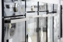Hornos eléctricos a estrenar en la tienda de dispositivo imágenes de archivo libres de regalías