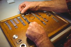 Horologist arranging watch strap on wooden board Royalty Free Stock Image
