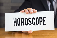 Horoscope, message on white card and hold by Royalty Free Stock Photography