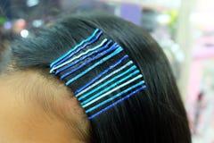 Horquilla del azul de los accesorios del pelo Mujer joven con las pinzas de pelo en pelo Imagen de archivo libre de regalías