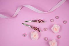 Horquillas de oro con la piedra preciosa rosada y la cinta rosada del lunar en fondo rosado Imagen de archivo libre de regalías