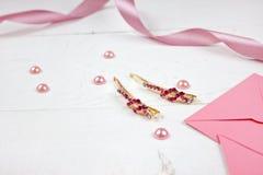 Horquillas de oro con la piedra preciosa rosada y la cinta rosada en fondo rosado Foto de archivo libre de regalías