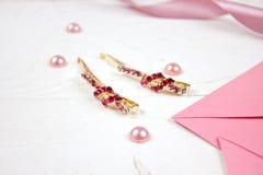 Horquillas de oro con la piedra preciosa rosada y la cinta rosada en fondo rosado Foto de archivo