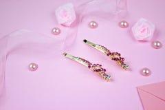 Horquillas de oro con la piedra preciosa rosada y la cinta rosada en fondo rosado Imagen de archivo libre de regalías