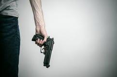 Horreur et sujet d'armes à feu : suicide avec une arme à feu sur un fond gris dans le studio photos stock