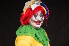 A horrible clown with a terrible make-up and hat laughing on a b Royalty Free Stock Photos