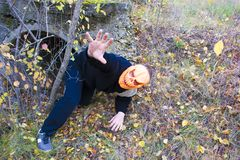 Horrible creature in the autumn forest in the evening. Happy Halloween. Pumpkinhead. A man with a pumpkin on his head climbs out of the pipe stock photos