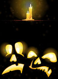 Horrible Jack o Lanterns and burning candles. Two pumpkin monsters with glowing eyes and burning candles on a dark background Stock Photography