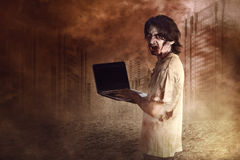 Horrible male zombies standing typing in laptop looking at behin Stock Photos