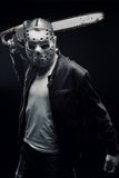 Horrible maniac. Man in mask with chainsaw posing over dark background stock photos