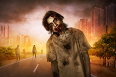 Horrible scary zombie walking around. On the burned city Royalty Free Stock Image