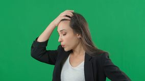 Horrible, stress, shock. Female portrait isolated at green screen background. Young emotional surprised woman clasping