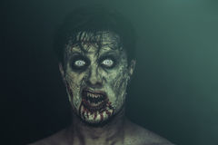 Horrible zombie. Bloody horrible zombie man screaming on black background. Halloween face makeup stock photo