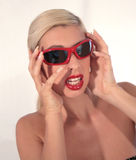 Horrified. A Pretty blond woman holding her hands up to her face with a horrified expression, with red sunglasses on royalty free stock images