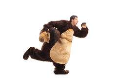 Horrified man in a bear costume running Stock Photo