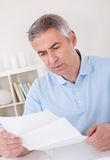Horrified old man reading a letter Stock Image