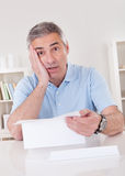 Horrified old man reading a letter Stock Images