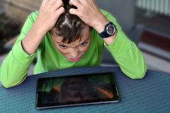 Horrified teenager boy. Horrified  teenager boy, his tablet computer  does not work Royalty Free Stock Image