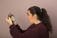 Horrified woman looking at the time. On an old fashioned alarm clock with her mouth wide open in shock Royalty Free Stock Image