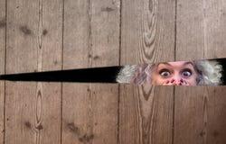 Horrified woman peeping through a gap stock photos