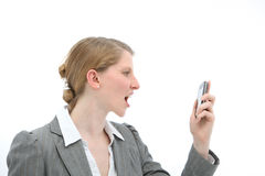Horrified woman reading text message on phone. Horrified woman standing reading a text message on her mobile phone which she is holding in her hand Royalty Free Stock Photography