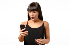 Horrified young woman looking at her mobile Royalty Free Stock Photo