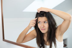 Horrified young woman looking in the mirror Royalty Free Stock Image