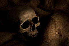 Horror. Scary dimly lit human skull laying on the gunny cloth Royalty Free Stock Photography